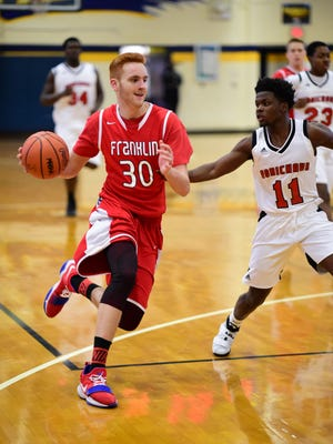 Livonia Franklin senior forward Mark Mettie (30) drives around a Dearborn Heights Robichaud player during the Patriots' season opener on Dec. 5. Mettie won that game with a slam dunk in the closing seconds of regulation.