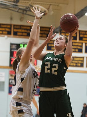 St. Johnsbury's Emilie Begin (22) leaps past Essex's Kylie Archer (50) for a lay up during the girls basketball game between the St. Johnsbury Hilltoppers and the Essex Hornets at Essex high school on Tuesday night January 5, 2016 in Essex.