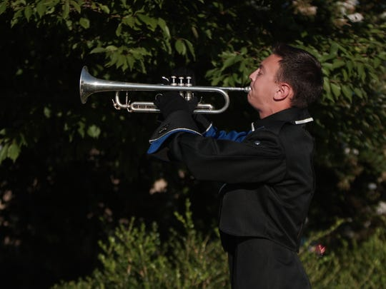Austin Grey, 17, a senior at Middletown High School, plays Taps during a memorial service honoring those who lost their lives on Sept. 11, 2001.
