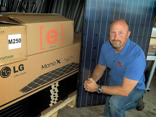 Ascom Electric President Jeff Georg poses with a 60-cell monocrystalline solar panel at  the Dover Township business.