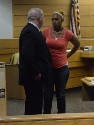 Jamie Moffitt talks with Battle Creek Detective Jeff Coons during court recess.