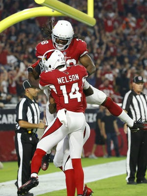 Arizona Cardinals wide receiver J.J. Nelson (14) and running back Andre Ellington (38) celebrate with wide receiver Brittan Golden (10) after his touchdown against the Oakland Raiders during the first quarter of their NFL game Saturday, Aug. 12, 2017, in Glendale, Ariz.