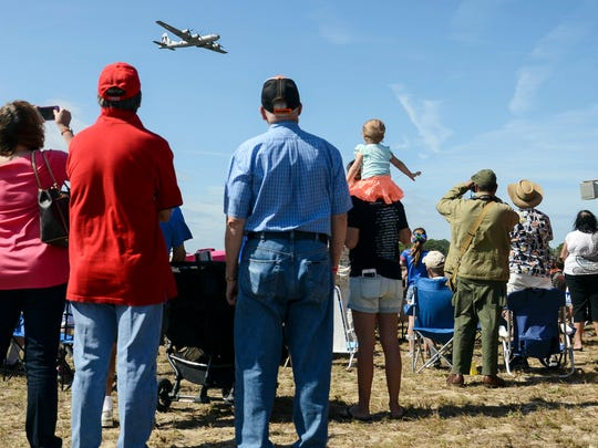 Spectators watch as a B-29 Superfortress flies overhead during the TiCo Warbird Air Show at Space Coast Regional Airport.