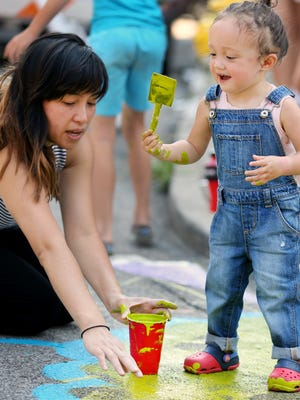 Ardea Zurich, 21 months, gets into the spirit of street painting with her mom, Jackie Pham, during Northside's Cincy Summer Streets. The art was sponsored by Art on the Street and depicted a scene from Northside, created by Rick Wolf.