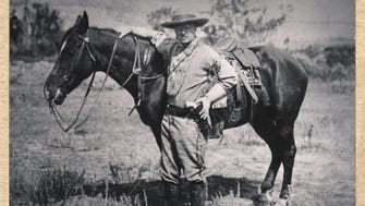 President Theodore Roosevelt stands with a saddled horse in the Badlands of western North Dakota.