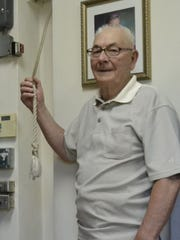 Harlin Mercier, 78, holds the rope that is pulled to