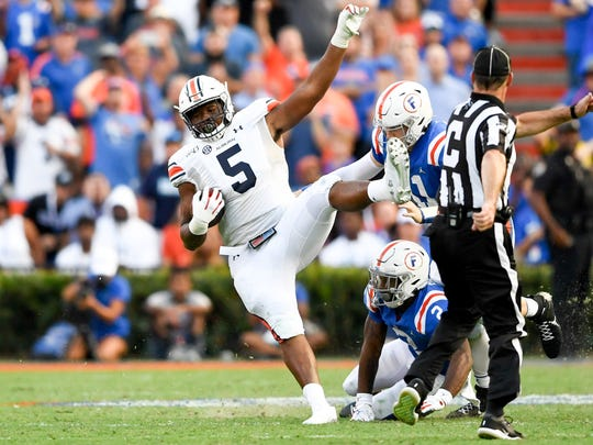 Oct 5, 2019; Gainesville, FL, USA; Auburn Tigers defensive tackle Derrick Brown (5) runs the ball after his interception during the fourth quarter against the Florida Gators at Ben Hill Griffin Stadium. Mandatory Credit: Douglas DeFelice-USA TODAY Sports