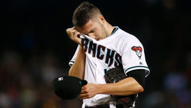 Arizona Diamondbacks' Patrick Corbin wipes sweat from his face on his way to giving up six runs to the San Diego Padres during the fourth inning of a baseball game Friday, Sept. 8, 2017, in Phoenix. (AP Photo/Ross D. Franklin)