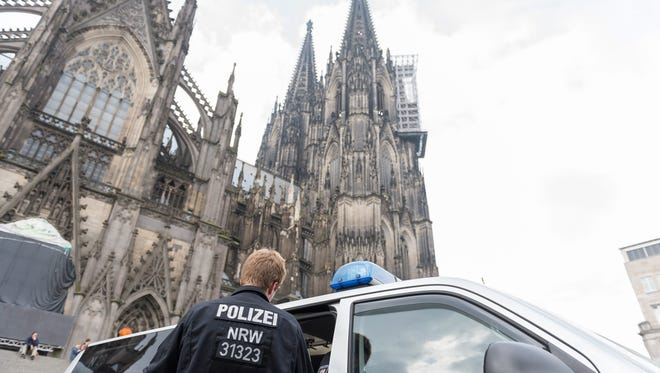 Police officers stand in front of the cathedral ahead of a rally in Cologne, Germany, July 31, 2016.