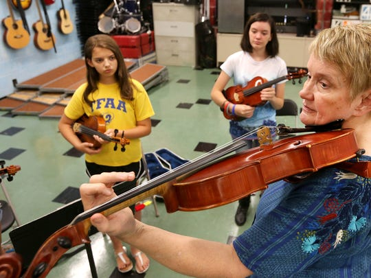 Mary Helen Law shows proper form during a strings camp at Thurman Francis Arts Academy, on Wednesday July 13, 2016.