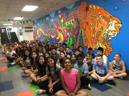 Students are shown with the mural by Joe Pimentel they