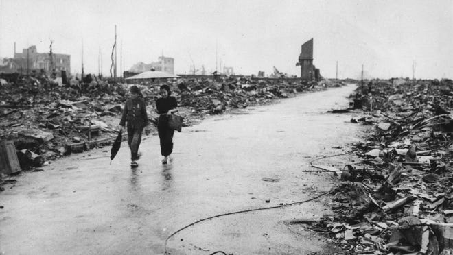 Two people walk through Hiroshima, Japan, a month after the first atomic bomb in history was dropped on the city.