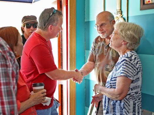 "Indianapolis Star reporter Robert King, left, shakes hands with Frank and Carolyn Speckman, during a ""Meet the Kings"" night at Tin Comet Coffee, Tuesday, June 3, 2014.  The Kings of Indy had a get-together at the coffee house having invited their friends, readers, and neighbors."