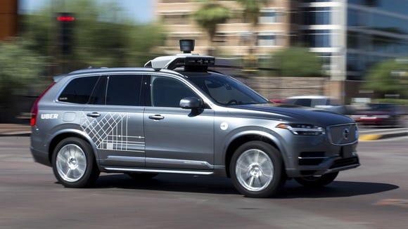An Uber vehicle cruises in Tempe, Ariz., on Aug. 25,