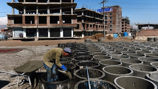 An Afghan construction worker makes concrete tubes on the outskirts of Kabul on March 18, 2014. A U.S. inspector general is investigating Pentagon reconstruction efforts in the country.