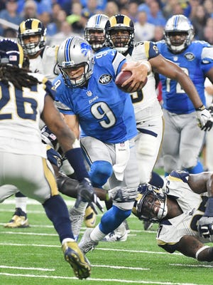 Lions quarterback Matthew Stafford doesn't slide but scrambles away from the Rams' Eugene Sims for a first down late in the fourth quarter Sunday in the Lions 31-28 win.