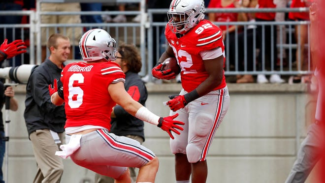 Ohio State Buckeyes defensive lineman and former Taft HS star Adolphus Washington (92) celebrates his interception return for a touchdown with teammate  and former Moeller HS star Sam Hubbard (6) during the second quarter at Ohio Stadium.