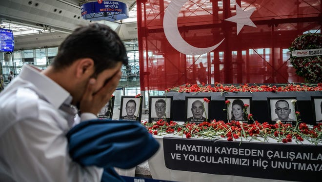 An airport employee mourns as he looks at pictures of killed airport employees at Istanbul's Ataturk airport international terminal on June 30, 2016, two days after the triple suicide bombing and gun attack.