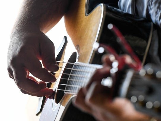 Musician Spencer Bloodworth strums out a tune for dinners