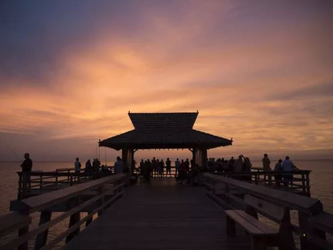 Tourists watch the sun set from the Naples Pier.