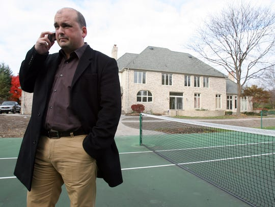 Former garbage company executive Charles (Chuck) Rizzo Jr., 46, of Bloomfield Hills was indicted on May 31, 2017, on multiple bribery and fraud charges stemming from trash contracts he won in Macomb County. He is accused of, among other things, using stolen money to build his Bloomfield Township mansion, which is pictured behind him.