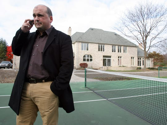 "Former garbage company executive Charles ""Chuck"" Rizzo Jr., 46, of Bloomfield Hills,  was indicted on May 31, 2017 on multiple bribery and fraud charges stemming from trash contracts he won in Macomb County.  He is accused of, among other things, using stolen money to build his Bloomfield Township mansion, which is pictured behind him in this photo."