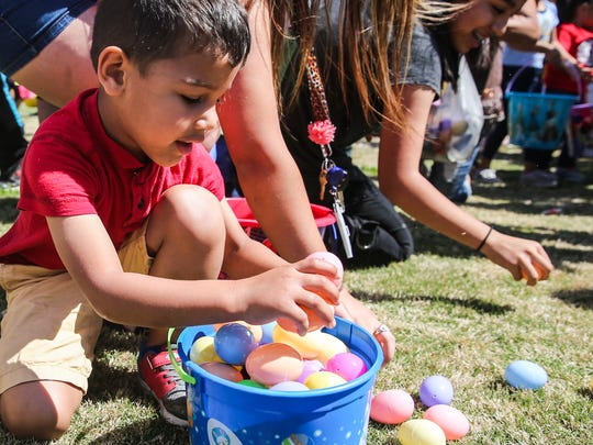 Children fill baskets with candy-filled eggs at Easter Fest Saturday, March 31, 2018, at Texas Bank Sports Complex.