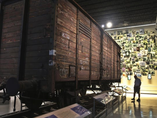 A visitor examines a box car, used by the Nazis to transport Jews to death camps, on display at the Florida Holocaust Museum in St. Petersburg on Jan. 27, International Holocaust Remembrance Day.