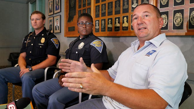 USPS letter carrier Glenn Bass, right, talks about the events that led to him, Indiana State Police Trooper Aryaun Smith, middle, and IPS Sgt. Josh Watson, left, saving the life of an elderly man along Bass' mail route. The three spoke of the incident at the Indiana State Police Post on E 21st Street  on Tuesday, Sept. 26, 2017.