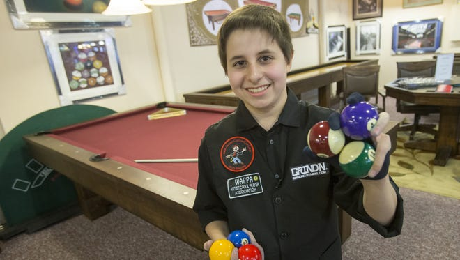 Matthew Webber, 14, Fishers, a pool trick-shot artist, holds balls at Jay Orner & Son Billiard Co. in Indianapolis in November 2015.