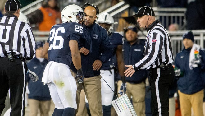 Penn State football coach James Franklin helps running back Saquon Barkley as he limps off the field Saturday night with a leg injury. Barkley's status for the Big Ten title game is uncertain.