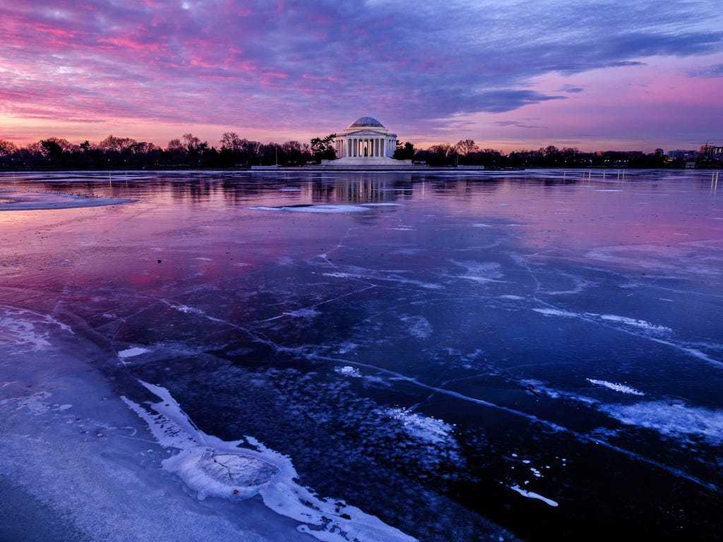 The Jefferson Memorial is reflected in the frozen surface of the Tidal Basin at daybreak in Washington. The Tidal Basin, famous for the Cherry Trees that surround it, is a sheet of ice after several days of bitter cold weather.