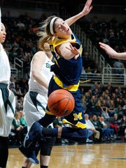 Michigan's Katelynn Flaherty loses the ball after she was fouled by Michigan State's Tori Jankoska, rear, during the first quarter of an NCAA college basketball game, Wednesday, Feb. 3, 2016, in East Lansing, Mich. (AP Photo/Al Goldis)