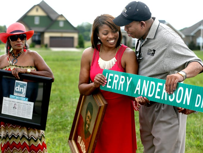 Vicky Anderson, center, the daughter of Jerry Anderson, who lost his life saving 2 teenage boys from drowning 25 years ago, accepts a street sign with her father's name from Murfreesboro City Council members Ron Washington, right and Madelyn Scales Harris, not pictured, during a street sign dedication for Jerry Anderson on Friday August 1, 2014. Jerry Anderson's sister Monica Green, left, holds a framed Daily News Journal article about Friday's dedication, that was presented to the family during the ceremony. Anderson also holds a framed painting of her Dad Jerry Anderson.