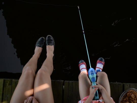 "Lansing resident Carly Cosper and her daughter Rosie, 5, fish at Adado Riverfront Park on Saturday, June 11, 2016 during the Grand American Fish Rodeo Festival. June 11 and 12 is Michigan's Free Fishing Weekend. ""We like to get out on the weekends,"" Carly said. ""(My daughters) are interested in the outdoors. When it's other people teaching the kids it's a different way to teach them things. They're more apt to listen to other people sometimes."" The U.S. Fish and Wildlife Service was there teaching children about different aquatic wildlife and how to fish."