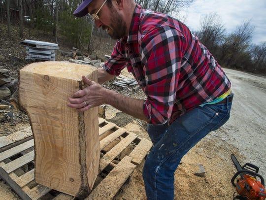 Clark Derbes uses a chainsaw to shape a pine log outside