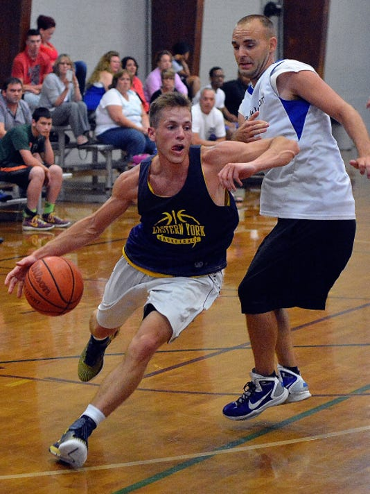 Broguen Nicholas, left of Wrightsville, drives past Dan Overmiller of AllTackle.com during the York Summer Basketball League Division II championship game at Voni Grimes Gymnasium on Tuesday. Nicholas led all scorers with 21 points in Wrightsville's 51-49 double-overtime victory.