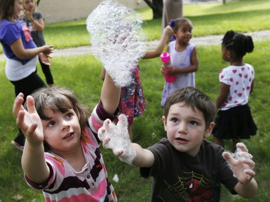 Cambria Whitaker, 4 (left) and T.J. Macomber, 4, tries to grab some floating soap bubbles Thursday, June 18, 2015, during Sunshine Storytime at the South Side Library in Des Moines.