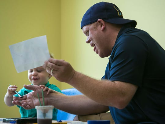 Kevin Brackney of Wilmington paints with his son Nicholas, 2, at the Children's Museum.