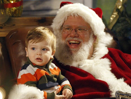 Jacob Cyran, 14 months, of Anderson Township, sits on Santa's lap during the Cincinnati Zoo's 29th Annual PNC Festival of Lights.