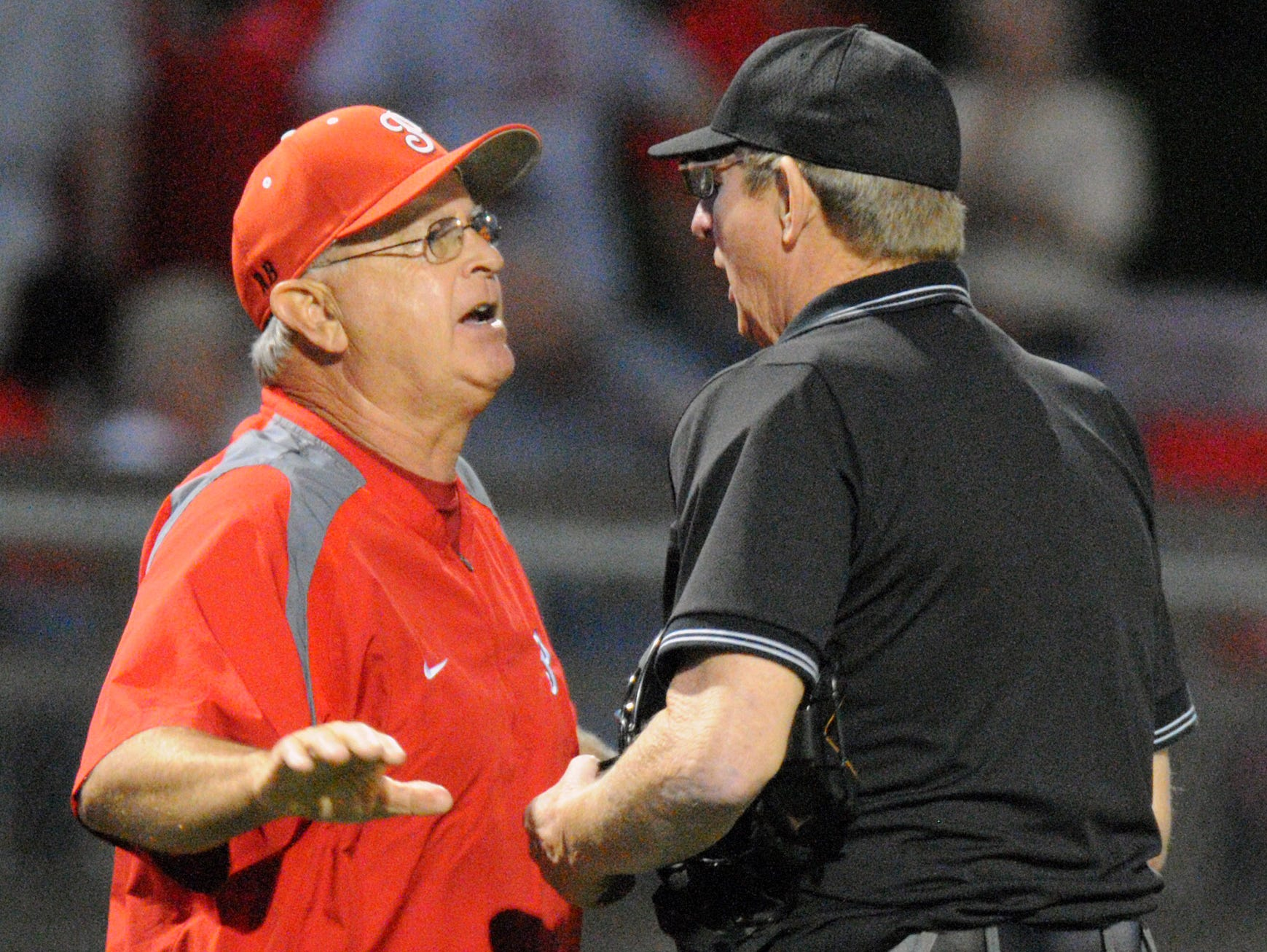 Petal's head coach Larry Watkins, left, argues with the umpire in a previous game against Oak Grove. The two high schools have an intense rivalry.
