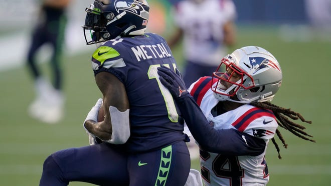 Seahawks wide receiver D.K. Metcalf, left, catches a pass and eludes Patriots cornerback Stephon Gilmore for a touchdown in the first half Sunday night.