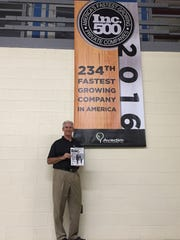 Steve Woody, CEO of Avadim Technologies, stands with a banner celebrating the company's growth, as recognized by Inc. magazine, in this 2016 photo. Appalachian Regional Commission funds will help provide access to expanded facilities for the company in Black Mountain.