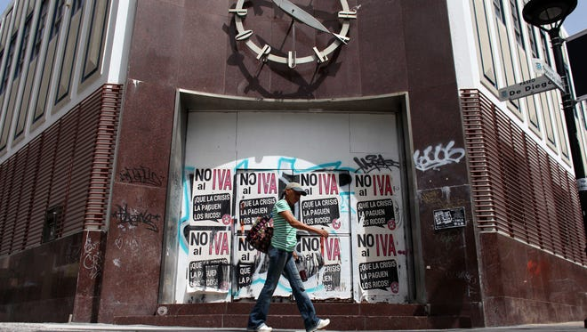 "A woman walks in front of a closed down bank in the neighborhood of Rio Piedras in San Juan, Puerto Rico on June 29, 2015. The bills on the closed bank doors read in Spanish ""No to the value added tax. Let the rich pay for the crisis."""