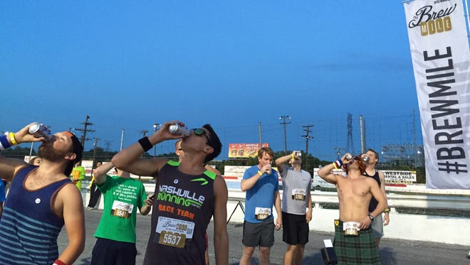 The elite heat drinks their first beer before taking off for Nashville's first-ever Brew Mile at the State Fairgrounds on Friday night.