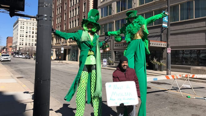 Erfan Ahmad poses with two people in costumes who were headed to Milwaukee's St. Patrick's Day Parade Saturday.