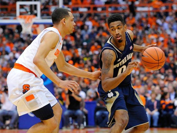 Notre Dame Fighting Irish guard Eric Atkins (0) controls the ball against the defense of Syracuse Orange guard Tyler Ennis (11).