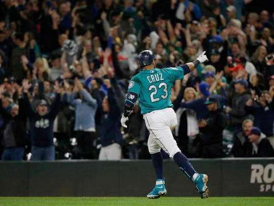 Seattle Mariners' Nelson Cruz  points to fans as he