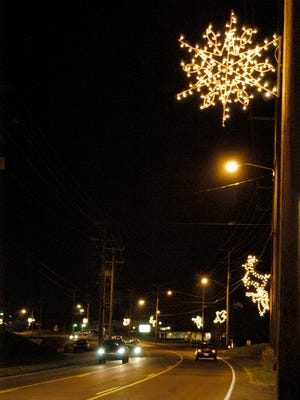 White Bluff's annual electric Christmas parade will roll west down Highway 70 at 4:30 p.m. Saturday. Pictured, town staff hung electric holiday decorations on downtown light poles along the parade route in late November.