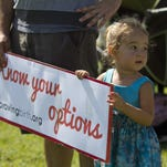 Guinevere Anders, 2, holds a sign at last year's Rally to Improve Birth in Cape Coral.
